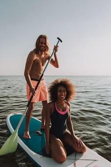 パドルと海で若い10代カップル行サーフィン。