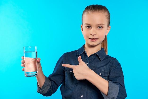 10代の少女は水のガラスを保持しています。