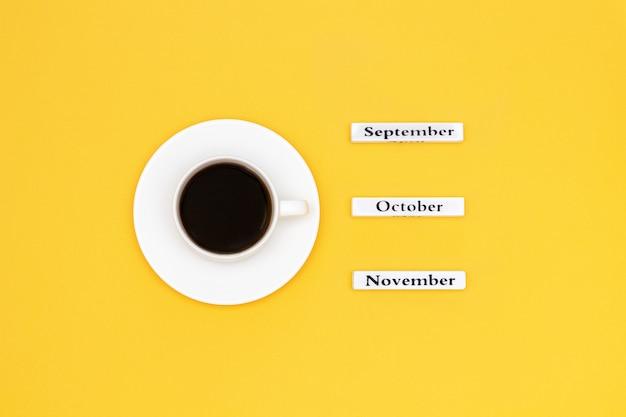 一杯のコーヒーとカレンダー11月10月9月黄色の背景に