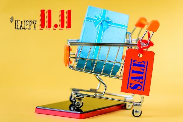 中国語の11.11単一の日の販売の概念。ミニショッピングカートとラベルタグ付きギフトボックス。