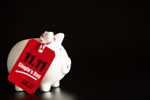 オンラインショッピング一日の販売の概念。赤いチケット11.11の販売タグは、ピギーバンクでぶら下がっている