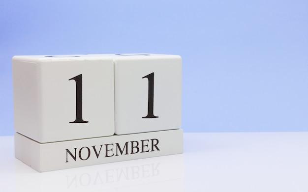 11 ноября день 11 месяца, ежедневный календарь на белом столе с отражением, с голубым фоном