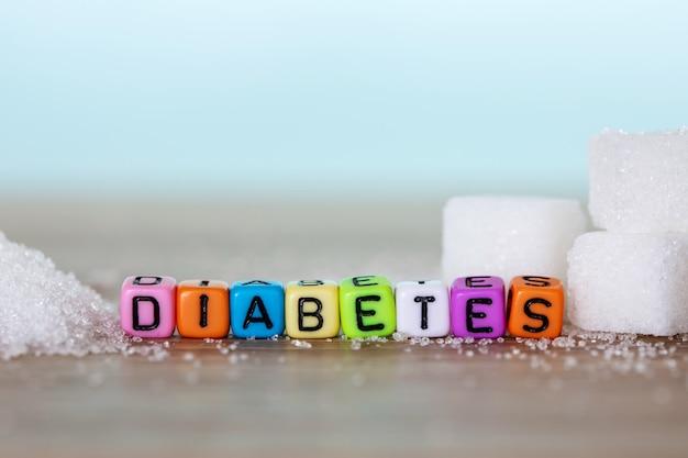 白い砂糖キューブと明るい青の背景を持つ木製のテーブル上の糖尿病単語のカラフルなアルファベットブロック、世界糖尿病デーの11月14日キャンペーンのための不健康な甘い食べ物のコンセプト