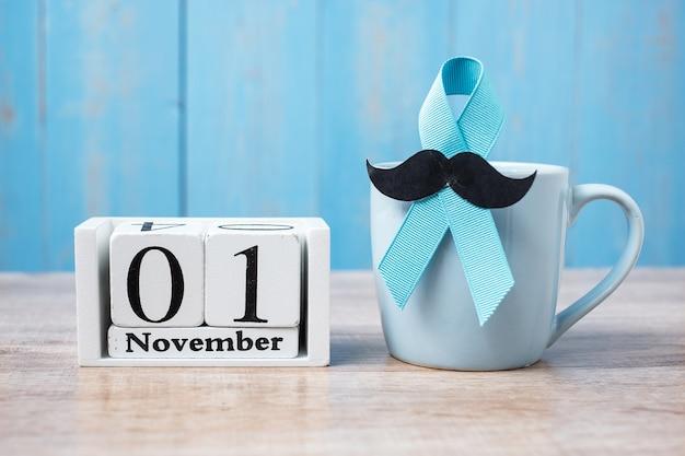 青いコーヒーカップ、青いリボン、黒い口ひげ、11月1日のカレンダー。 。父、国際男性デー、前立腺がん啓発