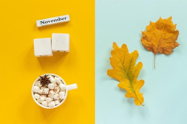 空白のキューブのモックアップと11月のカレンダーデータ、1杯のココア、黄色の紅葉