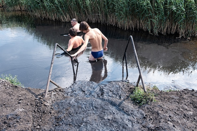 2021年7月11日、ロシア、ヤクート。癒しの泥の中の人々。有用な泥のあるミネラル塩湖。