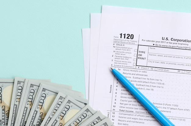 1120 tax form lies near hundred dollar bills and blue pen on a light blue