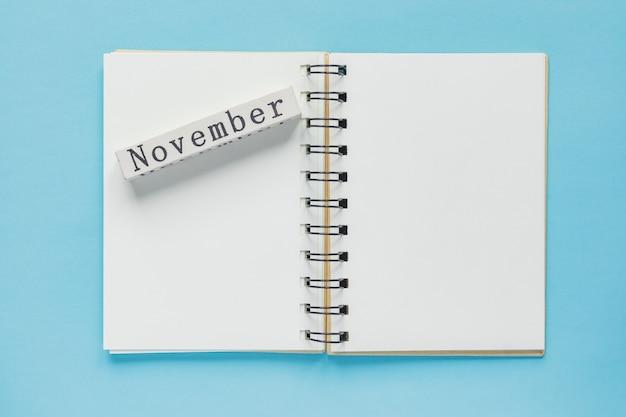 青のノートとメッセージと11月の木製カレンダーバーのきれいなスパイラルメモ帳