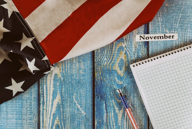 カレンダー年の11月月アメリカ合衆国空のメモ帳とオフィスの木製テーブルの上のペンで自由と民主主義のシンボルのアメリカ合衆国の旗