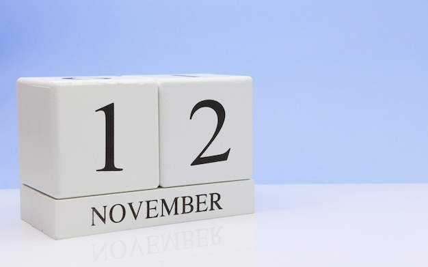 12 ноября день 12 месяца, ежедневный календарь на белом столе с отражением, с голубым фоном