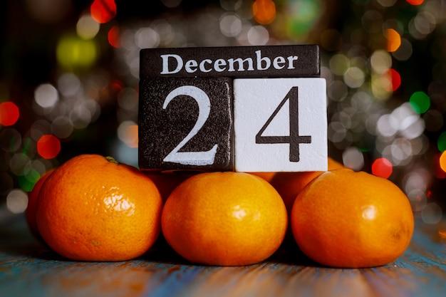 クリスマスイブ、クリスマスツリーライトの背景にみかんで12月24日木製キューブカレンダー。