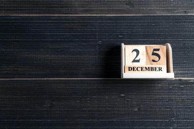 木製のブロックカレンダーは、木製の黒い背景に12月25日のクリスマスの日付に設定されています。