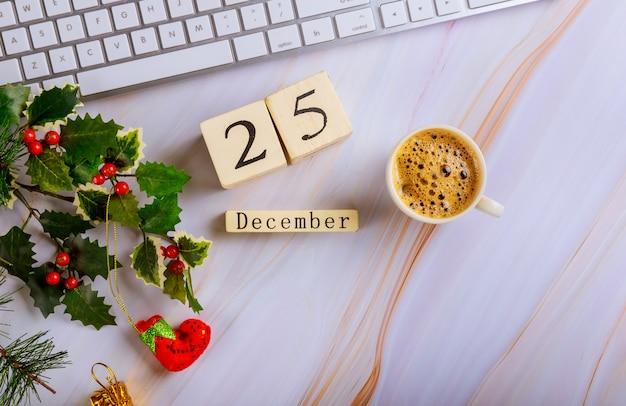 12月25日のクリスマスの日にコーヒーカップのコンピューターキーボードクリスマス組成物のあるオフィスデスク