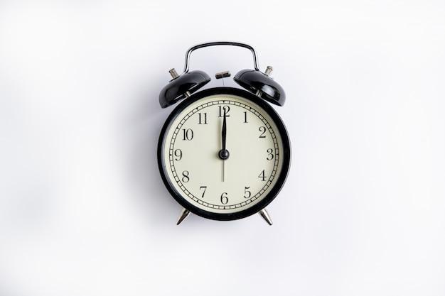 ダイヤル12時、白い背景に黒の目覚まし時計、6に目覚まし時計