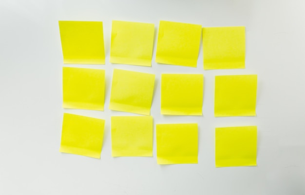 12 blank yellow sticky notes on white board