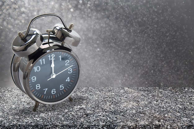 12 o'clock alarm clock on granite table with abstract background.