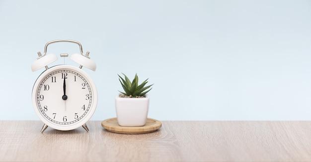 白丸目覚まし時計の12時。観葉植物と木製のテーブルの目覚まし時計。テキスト用のスペースを備えた最小限の構成。
