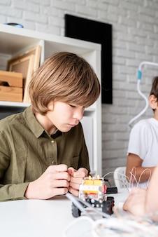 テーブルに座ってロボット車を構築する12歳の少年