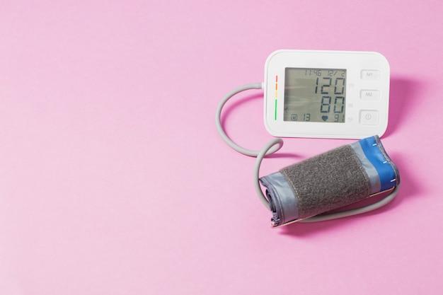 Современный тонометр на розовом столе, давление от 120 до 80 на мониторе