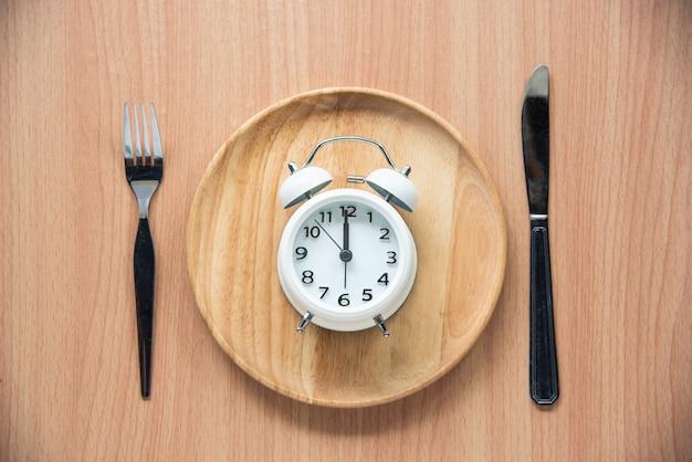 時計は昼の12時で、木の皿で昼食をとります。