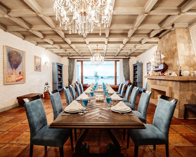 Ресторанный стол на 12 персон с синими стульями, камином, белыми кирпичными стенами и широким окном