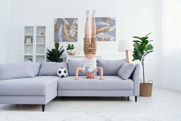 12歳のスポーティなアクロバット少年が頭の上に立っていて、自宅のソファに手を置いています。