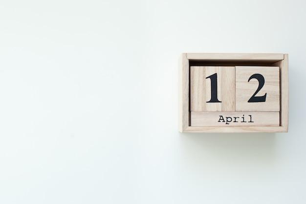 12 апреля пасха деревянный блок календарь на белом фоне изолированных стены. пасхальный. вид сверху с копией пространства. католическая пасха. деревенский деревянный декор дома. праздник весенней пасхи. вид сверху. праздновать