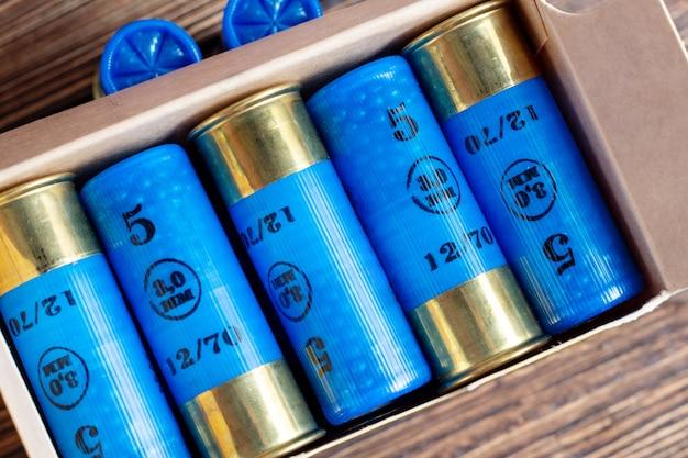 Цветные патроны калибра 12 калибра охотятся снаряды в коробке на коричневом деревянном фоне