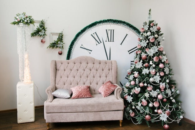 クリスマスと新年の装飾。クリスマスツリー、ソファ、12時を示す大きな時計