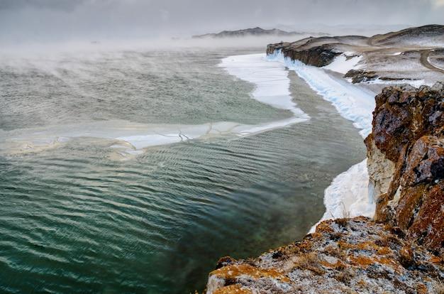 12月の寒さでバイカル湖と岩。フリーズアップの時間。流氷が水を泳いでいます。
