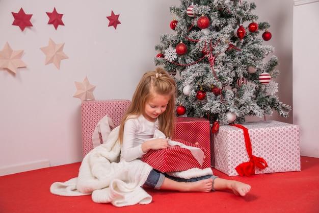 女の子はクリスマスパーティーのプレゼントを用意しました。クリスマスライトとリビングルームの装飾。新年のクリスマスツリーと花輪。魔法の幸せな12月