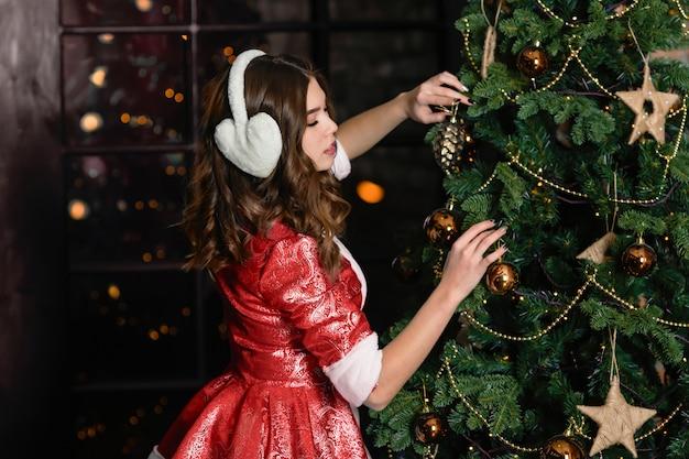 Россия, тольятти - 13 ноября 2018: рождество символов снегурочка. девушка в новогоднем костюме украшает елку