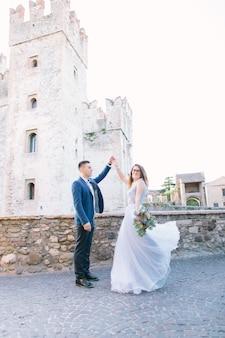 Любовь в италии, сирмионе. красивая пара кавказских в роскошной одежде позирует возле замка скалигер (13-го века) в сирмионе на озере гарда недалеко от вероны, италия