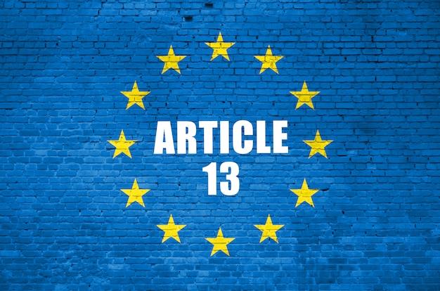 青いレンガの壁に第13条碑文と欧州連合の旗
