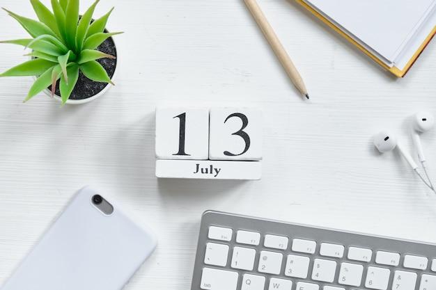 Концепция календаря месяца тринадцатого июля тринадцатого июля на деревянных блоках.