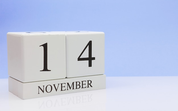 14 ноября день 14 месяца, ежедневный календарь на белом столе с отражением, с голубым фоном