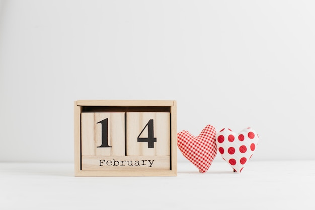 14 ebruary on wooden calendar near handmade hearts