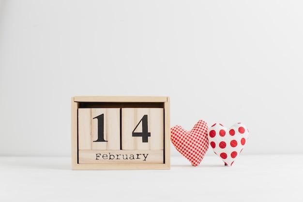14 ebruary on wooden calendar near handmade hearts