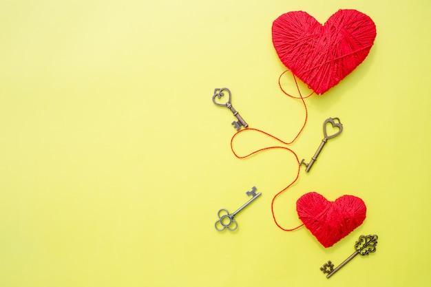 2月14日、愛のシンボルとしての心を持つキー。黄色の壁に赤いハートのグリーティングカード。バレンタインデーの壁。私の心のコンセプトの鍵。心への道。バレンタインデー。コピースペース
