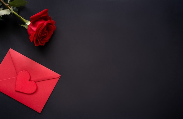 14 день святого валентина фон. красные цветы розы и конверт с сердцем на черном фоне, вид сверху, копией пространства