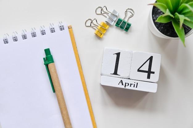 Дата на белых деревянных кубиках - четырнадцатое, 14 апреля на белом столе. вид сверху.