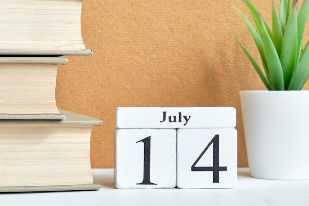Концепция календаря месяца 14-ое июля четырнадцатого дня на деревянных блоках.