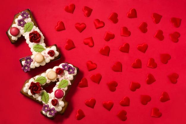 Торт ко дню святого валентина с 14 цифрами и красными сердечками на красном