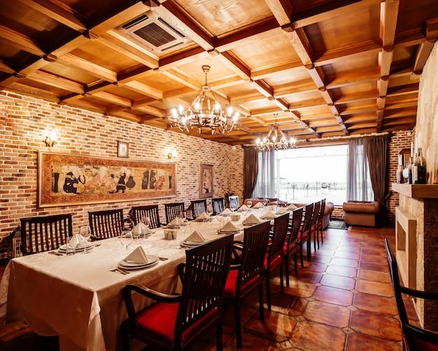 レンガの壁、広い窓、木の天井のあるレストランホールの14人用のレストランテーブル