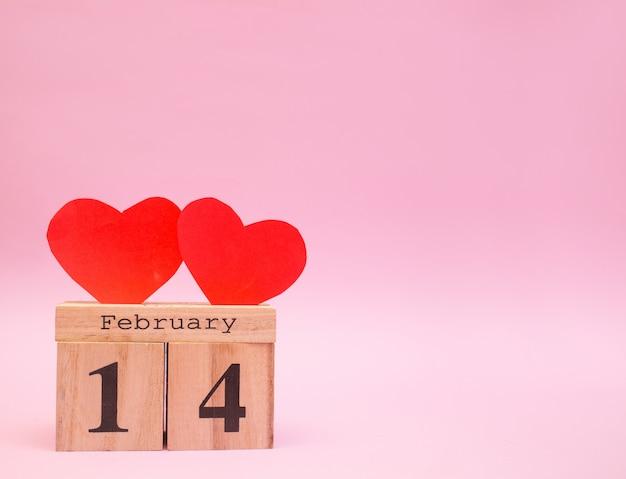 Деревянный календарь на розовом фоне с красными сердцами. день святого валентина 14 февраля