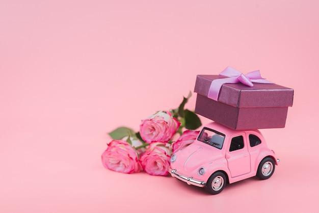 Розовый ретро игрушечный автомобиль поставляет подарочную коробку на розовом фоне. открытка 14 февраля, день святого валентина. доставка цветов. женский день