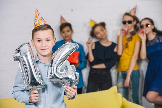 Мальчик с днем рождения держит в руках серебряные воздушные шарики с цифрами 14, а его друзья стоят за ним
