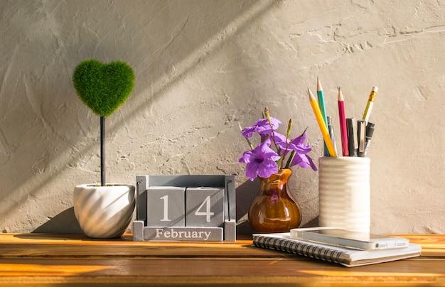 Винтажный деревянный календарь на 14-ое февраля с зеленым сердцем на деревянной влюбленности таблицы и предпосылке концепции дня валентинки, фоне.