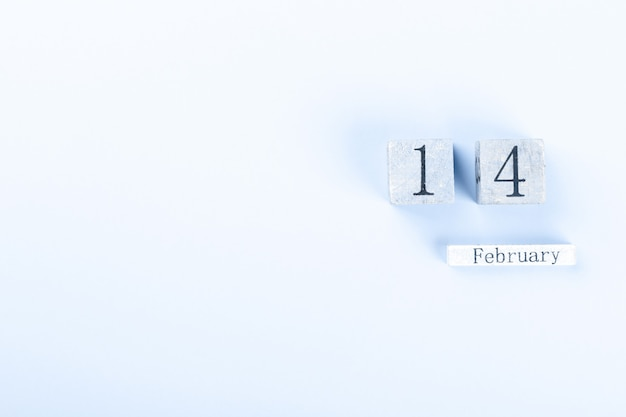 Деревянный блок календаря 14 февраля на синем фоне. день святого валентина