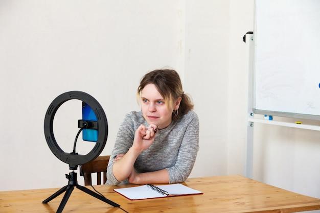 15 세 여성 블로거가 생방송을 주도하고 라이트 룸에서 링 램프로 자신을 밝힙니다.